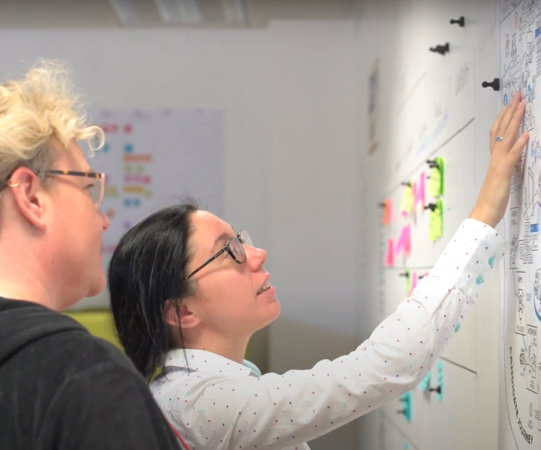 Rachel Murphy and Zoë Gould looking at a board of post it notes