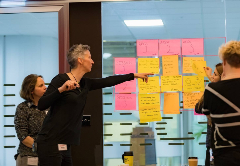 Members of the team pointing at post it notes