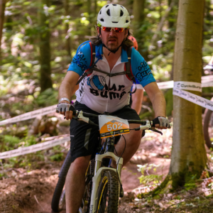 Andrew Larcombe riding a mountain bike through woods