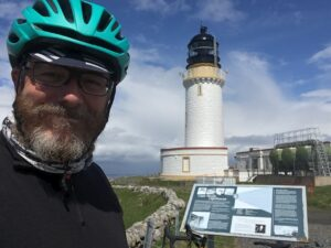 Sean Phelan in front of a lighthouse wearing a cycle helmet