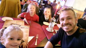 Smiling Tom Surtees and his three girls